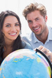 Portrait of a beautiful couple looking at a globe Royalty Free Stock Photo