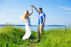 Portrait of beautiful couple in love dancing on seacoast Stock Photography