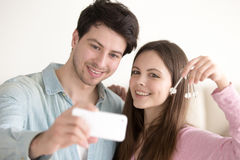 Portrait of beautiful couple making selfie on mobile holding key. Young couple taking self portrait with smartphone showing keys, excited by apartment purchase Royalty Free Stock Photography