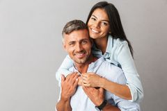 Portrait of beautiful couple man and woman in basic clothing smiling and hugging together, isolated over gray background. Portrait of beautiful couple men and royalty free stock image