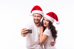 Portrait beautiful couple in Santa hats in love taking romantic self portrait Royalty Free Stock Image