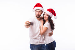 PORTRAIT beautiful couple in Santa hats in love taking romantic self portrait. Christmas young beautiful couple in Santa hats in love taking romantic self Royalty Free Stock Photography