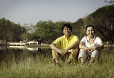 Portrait of beautiful couple sitting on ground in park Royalty Free Stock Image