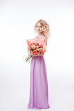Portrait of beautiful curly blondy woman with perfect make-up. Holding bouquet. Long evening purple dress Royalty Free Stock Photography