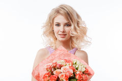 Portrait of beautiful curly blondy woman with perfect make-up. Holding bouquet Royalty Free Stock Images
