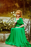 Portrait of a beautiful curly haired pregnant girl in a green dr royalty free stock image