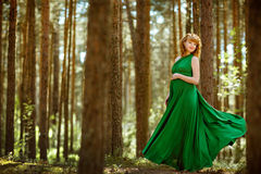 Portrait of a beautiful curly haired pregnant girl in a green fl royalty free stock images