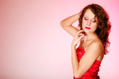 Portrait beautiful curly woman girl in red dress on pink. Copy space. Royalty Free Stock Photo
