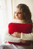 Portrait of beautiful curly woman posing with red cushion at win Stock Images