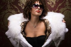 Portrait of beautiful curly young girl in furs Stock Images