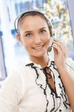 Portrait of beautiful customer service operator. Using headset, smiling happily Stock Photos