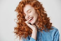 Portrait of beautiful cute ginger girl laughing smiling with closed eyes over white background. Stock Image