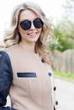 Portrait of a beautiful cute funny girl in sunglasses with a beautiful smile in a coat walks on city streets Stock Images