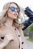 Portrait of a beautiful cute funny girl in sunglasses with a beautiful smile in a coat walks on city streets Stock Photo