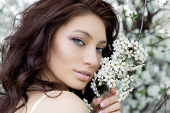 Portrait beautiful cute sweet sexy girl bride with gentle eye make-up full lips in white light dress walks in lush gard Royalty Free Stock Images