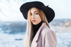 Portrait of a beautiful cute woman with natural make-up with clean skin in a stylish elegant hat in a pink coat stock photography