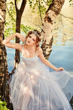 Portrait of beautiful dancer in nature. Beautiful ballerina in a white dress relaxing outdoors by the river Stock Photos