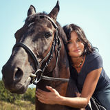 Portrait of beautiful dark-haired woman on a horse. Stock Image