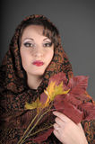 Portrait of a beautiful dark-haired woman with a scarf on her head and autumn leaves. In the hands on a gray background in studio Stock Image