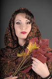 Portrait of a beautiful dark-haired woman with a scarf on her head and autumn leaves. In the hands on a gray background in studio Royalty Free Stock Photography