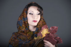 Portrait of a beautiful dark-haired woman with a scarf on her head and autumn leaves Stock Image