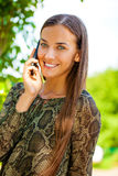Portrait of beautiful dark haired young woman speaking on mobile Royalty Free Stock Photos