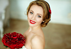 Portrait of beautiful delicate sensual brown-haired girl in a white dress with an unusual bouquet of red rose petals, smiling hap stock images