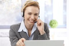 Portrait of beautiful dispatcher. Portrait of beautiful young female dispatcher using headphones, smiling, looking at camera Stock Image