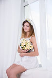 Portrait of beautiful dreaming bride in short white dress with f Stock Photography