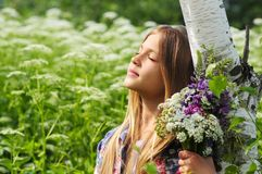 Portrait of a beautiful dreaming girl with a bouquet of flowers. Some white birch Royalty Free Stock Images