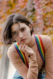 Portrait of a beautiful dreaming girl in multi-colored suspenders royalty free stock image