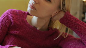 Portrait of beautiful dreamy blonde woman posing to photograph indoor. Close up stock video