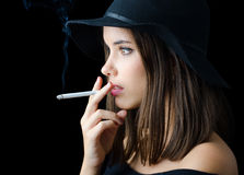 Portrait of beautiful elegant girl smoking cigarette isolated on black Royalty Free Stock Photography