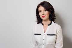 Portrait of beautiful elegant woman in a bright white shirt with bright makeup and red lipstick on a white background in studio Stock Photography