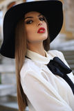 Portrait of beautiful elegant woman with dark hair in black hat Royalty Free Stock Photography