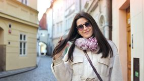 Portrait of beautiful elegant woman in sunglasses posing at historic building background. Looking at camera. Medium shot stylish young female tourist smiling stock video