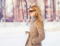 Portrait beautiful elegant woman wearing a coat jacket and sunglasses in city. Profile view Stock Photography
