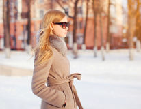 Portrait beautiful elegant woman wearing a coat jacket and sunglasses in city. Profile view Stock Photos
