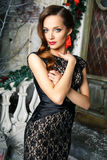 Portrait of beautiful elegant young woman in gorgeous evening dress over christmas background Royalty Free Stock Images