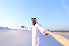 Portrait of beautiful Emirate male tourist guide, who holds woma. Cheerful Arab male with kindly smile on face leads woman`s arm from camera and shows desert Royalty Free Stock Photography