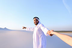 Portrait of beautiful Emirate male tourist guide, who holds woma. Cheerful Arab male with kindly smile on face leads woman`s arm from camera and shows desert Royalty Free Stock Photos