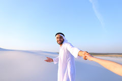 Portrait of beautiful Emirate male tourist guide, who holds woma. Cheerful Arab male with kindly smile on face leads woman`s arm from camera and shows desert Stock Images