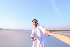 Portrait of beautiful Emirate male tourist guide, who holds woma. Cheerful Arab male with kindly smile on face leads woman`s arm from camera and shows desert Stock Photos