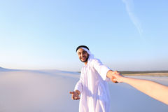 Portrait of beautiful Emirate male tourist guide, who holds woma. Cheerful Arab male with kindly smile on face leads woman`s arm from camera and shows desert Royalty Free Stock Images
