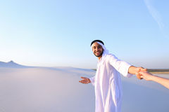 Portrait of beautiful Emirate male tourist guide, who holds woma. Cheerful Arab male with kindly smile on face leads woman`s arm from camera and shows desert Stock Photo