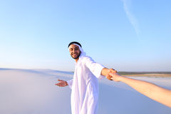 Portrait of beautiful Emirate male tourist guide, who holds woma. Cheerful Arab male with kindly smile on face leads woman`s arm from camera and shows desert Royalty Free Stock Photo
