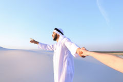 Portrait of beautiful Emirate male tourist guide, who holds woman. Cheerful Arab male with kindly smile on face leads woman`s arm from camera and shows desert Stock Images