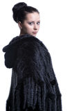 Woman in luxury black color fur coat looking back  Stock Photography