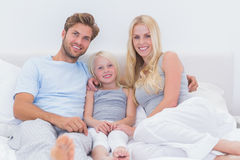 Portrait of a beautiful family in the bed Stock Image