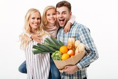 Portrait of a beautiful family holding paper shopping bag. Full of groceries isolated over white background royalty free stock photos